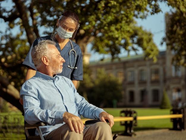 Giovane infermiera premurosa che indossa una visiera e una maschera che parla con un uomo maturo che spinge il paziente in sedia a rotelle
