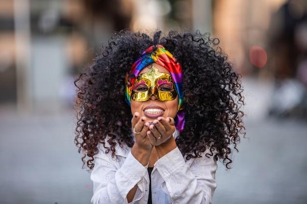 Festa carnaval. donna brasiliana capelli ricci in costume che soffia coriandoli