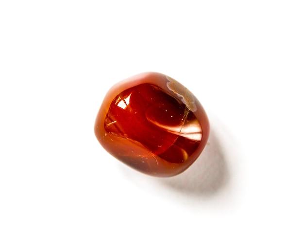 Pietra preziosa dell'agata corniola isolata su un fondo bianco