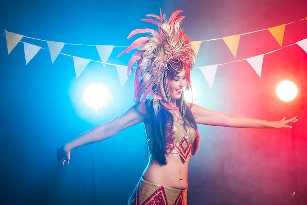 Carnevale, danza del ventre e concetto di vacanza - bella ballerina di samba femminile che indossa un costume d'oro e