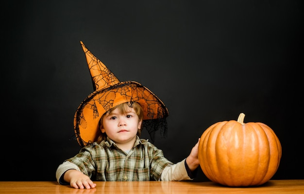 Costume di carnevale felice halloween bambino che gioca dolcetto o scherzetto bambino con cappello da strega nascosto a halloween