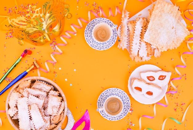 Maschera di carnevale, due tazze di caffè aromatico, dolci e coriandoli su uno sfondo giallo. decor per una vacanza tradizionale italiana. copia spazio. disteso