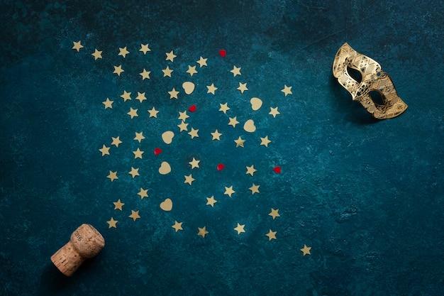 Maschere di carnevale, bottiglia di champagne e coriandoli glitter oro.