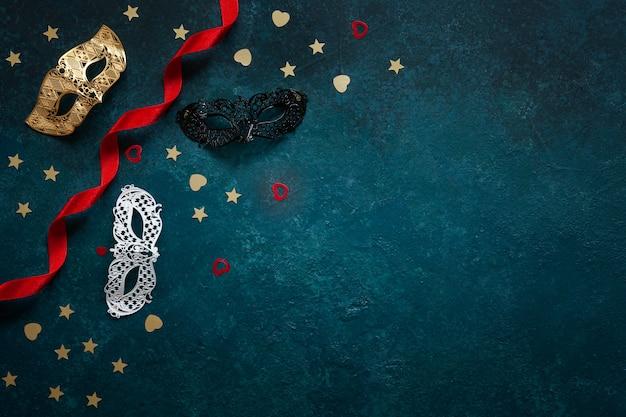 Maschere di carnevale e coriandoli glitter oro. vista dall'alto, close up su sfondo blu