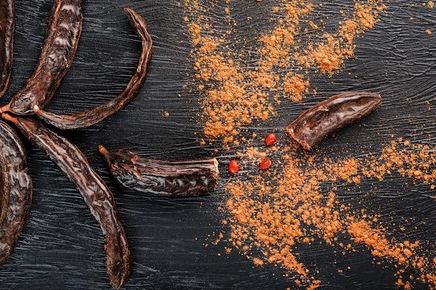 Cioccolato di carruba e polvere di frutta di carruba sulla superficie scura