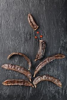 Frutto di carruba su una superficie strutturata nera