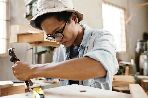 Il carpentiere si è concentrato sull'estrazione di pezzi dalla superficie del legno durante la realizzazione di un mobile