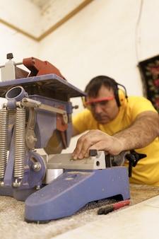 Falegname che taglia un pezzo di legno per mobili nel suo laboratorio di falegnameria, usando una sega circolare e indossando occhiali di sicurezza e cuffie antirumore.