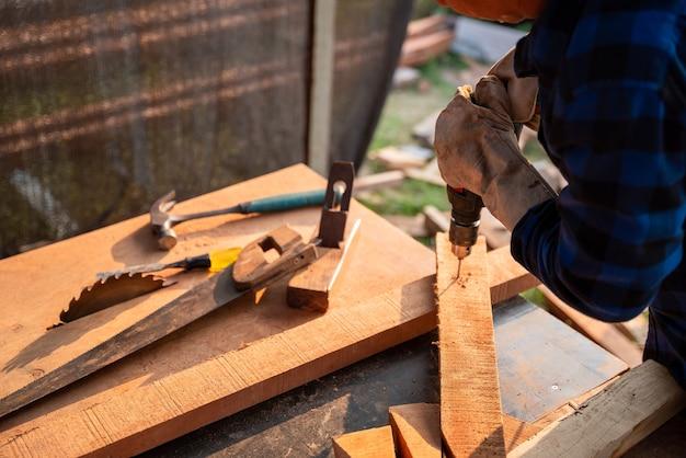 Il carpentiere fa un buco nel legno con un trapano elettrico.