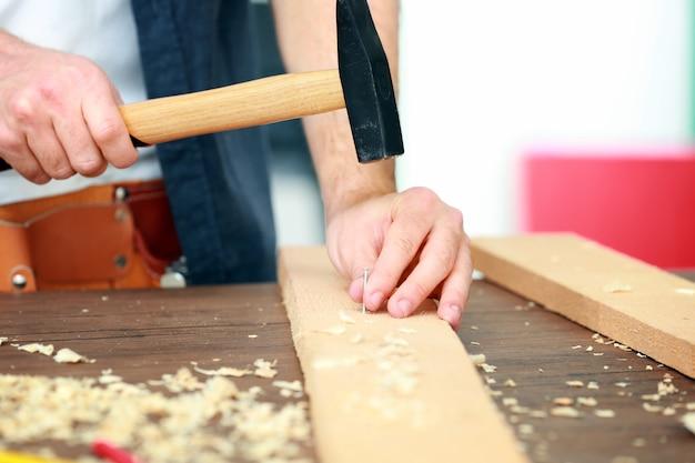 Carpentiere che guida il chiodo nella tavola di legno in officina, primo piano