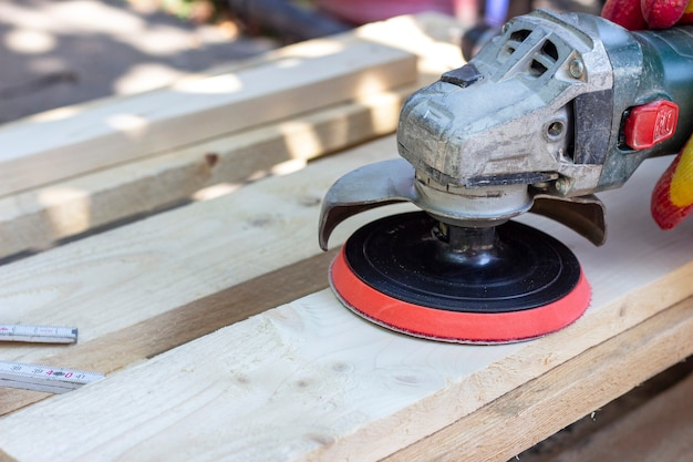 Il carpentiere macina il legno, trattamento superficiale del legno con una smerigliatrice. falegnameria, soppalco