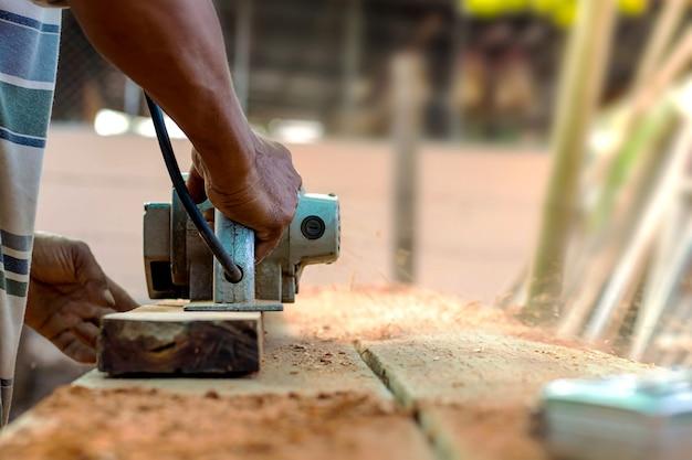 Una mano del falegname che tiene un aereo elettrico che lavora su un pavimento di legno
