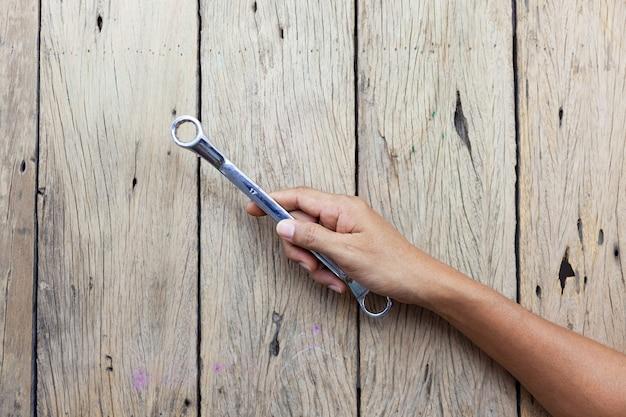 Mano del carpentiere che tiene la chiave numero 17 sul vecchio fondo della tavola in legno.