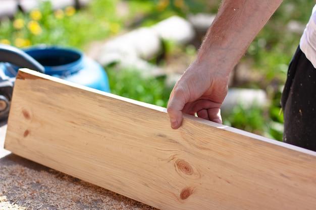 Falegname tenendo la tavola di legno