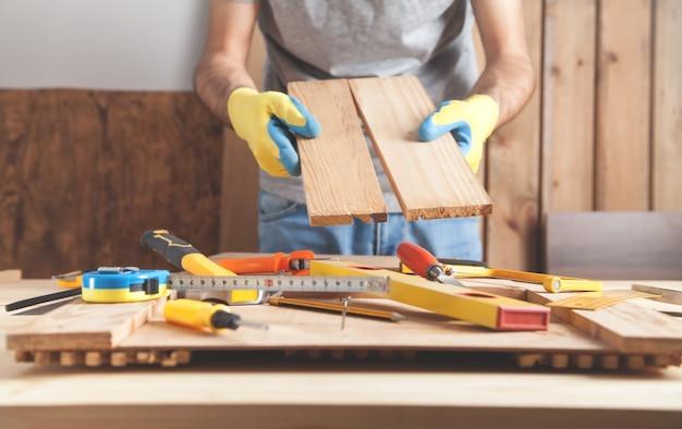 Carpentiere che tiene le plance di legno. industria della lavorazione del legno