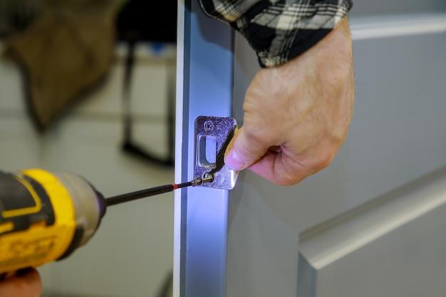 Installazione del carpentiere alla serratura della porta di legno interna di un appartamento