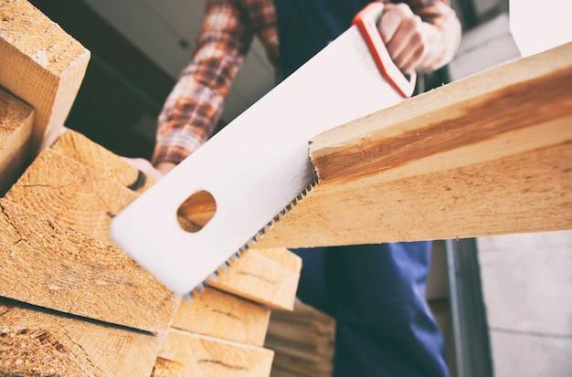 Il carpentiere sta tagliando la tavola di legno con la sega