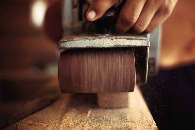 Un falegname sta levigando il legno con una carta vetrata.