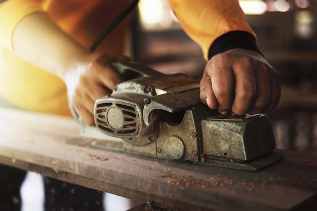 Il carpentiere sta usando gli strumenti per pulire il legno, raddrizzare il legno.