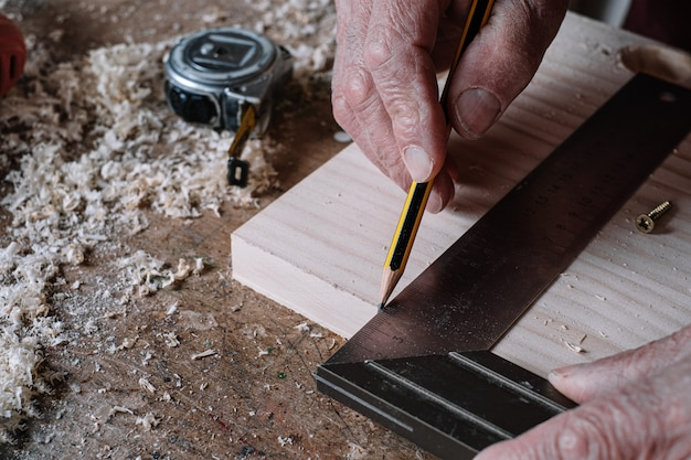 Falegname che effettua misurazioni su un tavolo con una matita e un quadrato di metallo