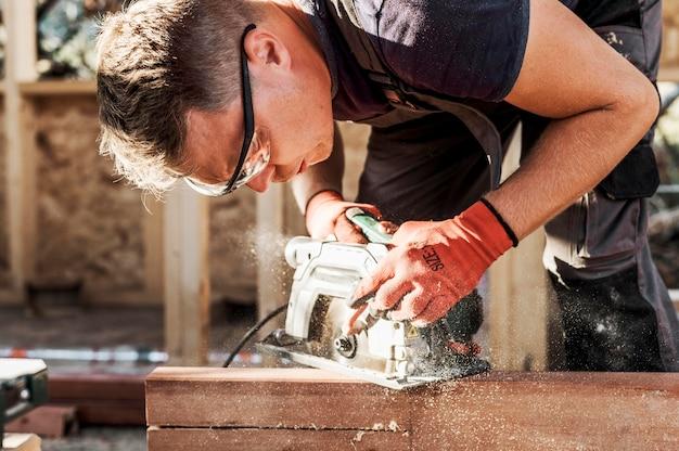 Uomo del carpentiere che taglia il legno con la macchina