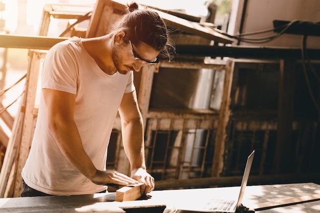 Falegname uomo che lavora nel laboratorio di legno mobili con abilità professionale operaio di persone reali.