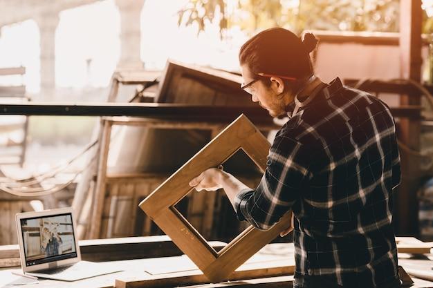 L'uomo del carpentiere che lavora nel laboratorio di bricolage impara da online. autoformazione dallo studio di e-learning su internet che realizza mobili dal video nel computer portatile durante il lavoro di blocco da casa.
