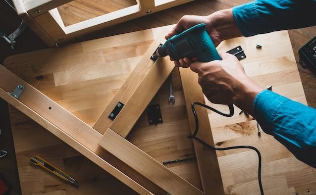 Uomo del carpentiere che lavora con trapano e mobili, fissaggio o riparazione di casa