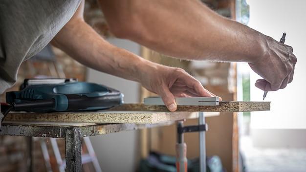 Il falegname misura il legno con uno strumento angolare e prende appunti.
