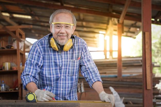 Gli uomini del falegname lavorano sulle misure del legno in una falegnameria.