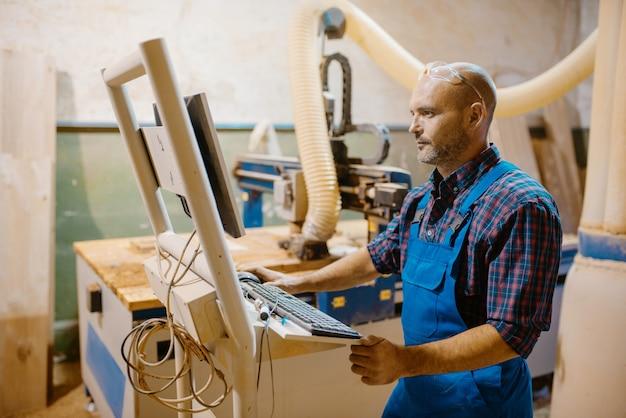 Carpenter al pc lavora con macchine per la lavorazione del legno, industria del legname, carpenteria moderna. lavorazione del legno in fabbrica di mobili, produzione di prodotti di materiali naturali