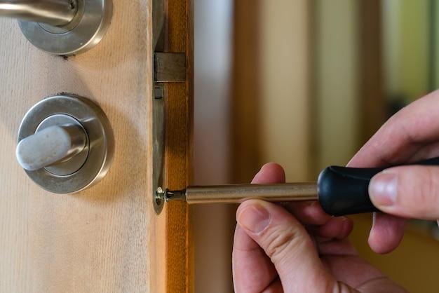 Carpentiere che ripara la serratura della porta. installazione di una maniglia della porta. tuttofare che stringe la cerniera della porta. mani del riparatore con un cacciavite. fabbro che avvita il bullone nella porta di legno