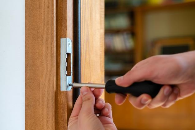 Carpentiere che ripara la serratura della porta.