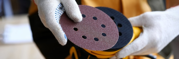 Il carpentiere sostituisce il pezzo di ricambio per la levigatrice. strumento per la finitura di superfici in legno. attrezzatura per rettifica commerciale. riparazione e rinnovo di mobili in legno.