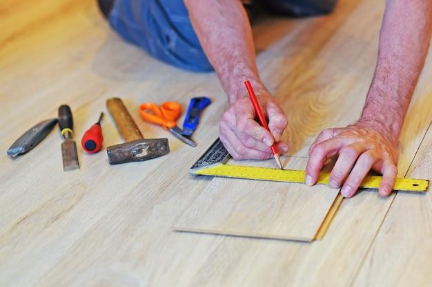 Le mani del falegname segnano sulla tavola laminata. ci sono strumenti nelle vicinanze.