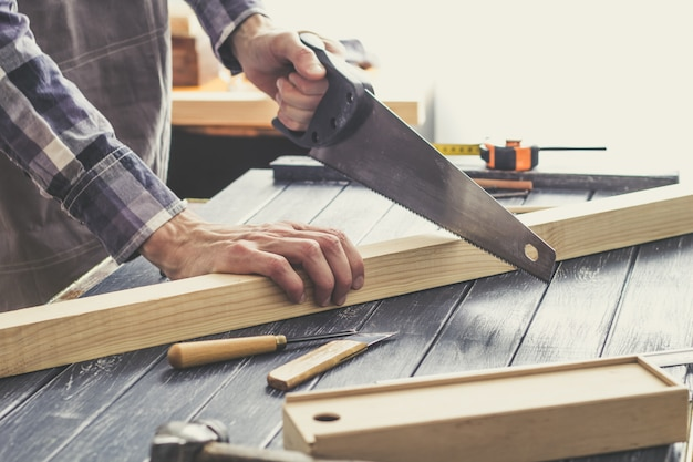 Carpenter segare una tavola di legno in officina.