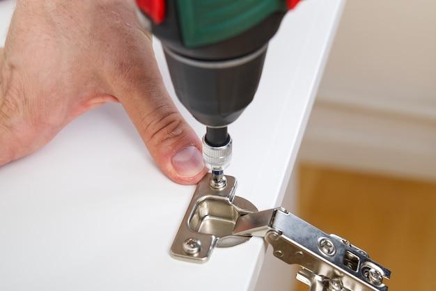 Il carpentiere avvita la cerniera sul concetto di servizio di montaggio del mobile della porta del mobile