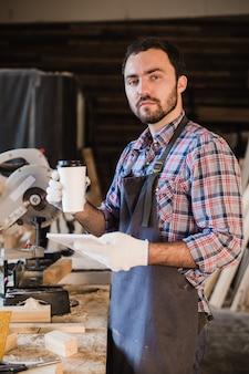 Carpentiere che prende un taccuino della tenuta della pausa caffè davanti alla sega circolare alla sua officina