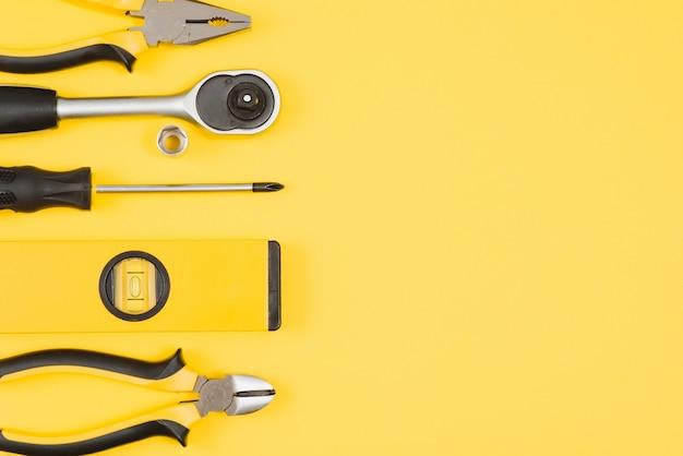 Strumenti del carpentiere impostati su sfondo giallo, vista dall'alto