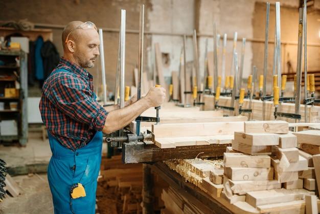 Falegname in uniforme blocca la tavola in una morsa, lavorazione del legno, industria del legname, falegnameria. lavorazione del legno in fabbrica di mobili, produzione di prodotti di materiali naturali