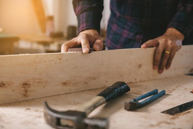 Il carpentiere usa carta vetrata su legno. l'industria della costruzione, i lavori domestici fanno da soli.