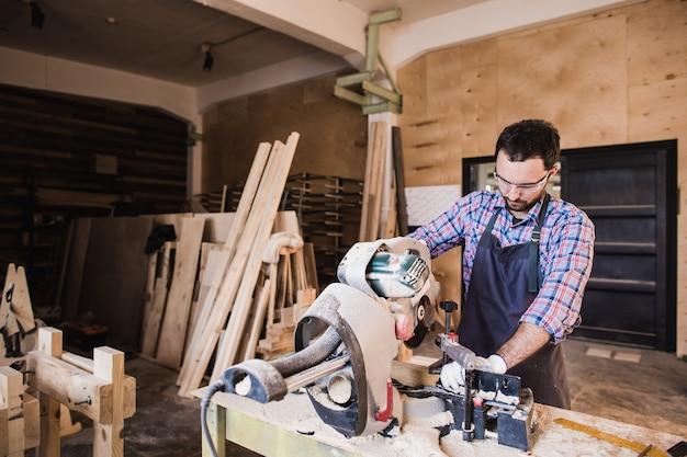 Falegname con sega circolare per legno nella sua bottega