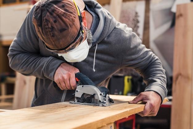 Carpentiere con maschera facciale che taglia una tavola di legno con una sega circolare elettrica