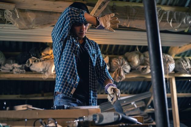 Carpentiere con una sega a mano che sega una tavola di legno in officina