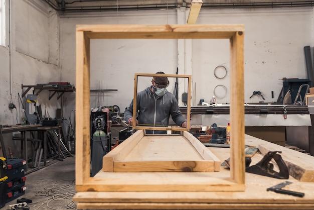 Carpentiere con maschera che costruisce cornici quadrate in legno