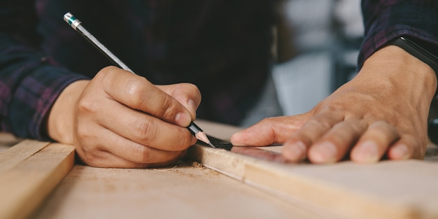 Carpentiere con una matita e un segno di righello sul bordo di legno sul tavolo. edilizia, lavori domestici fai da te.