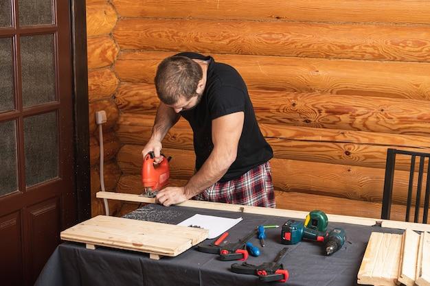 Falegname in abiti da lavoro e proprietario di una piccola azienda falegname sega e lavora i bordi di una barra di legno