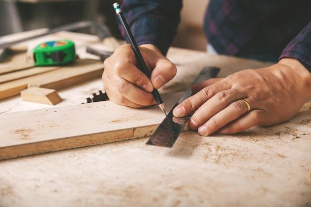 Carpentiere che lavora, martello, metro a nastro e pinze da taglio