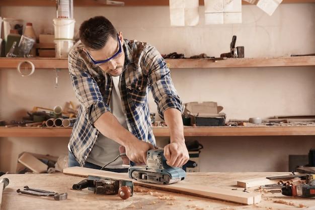Carpentiere che lavora con la levigatrice elettrica in negozio