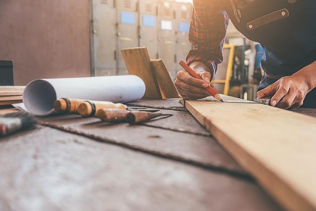 Carpentiere che lavora con l'attrezzatura sulla tavola di legno nel negozio di carpenteria.